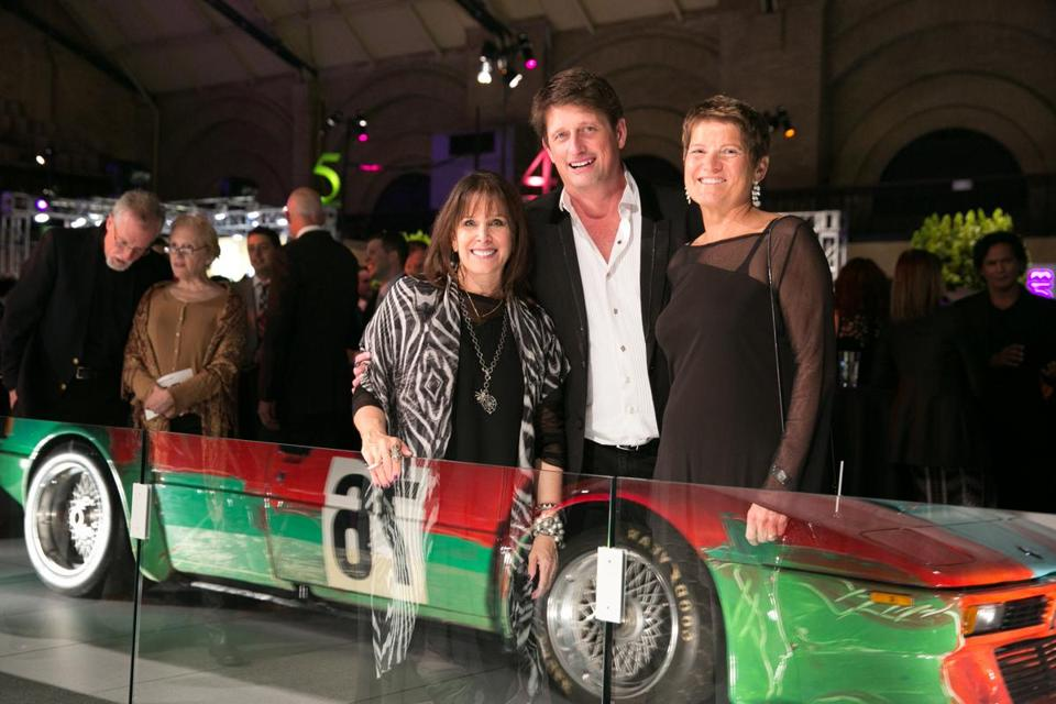 ARTcetera co-chairs Barbara Lee (left) and Bill Emery, with AIDS Action CEO Rebecca Haag, in front of Andy Warhol's Art Car.